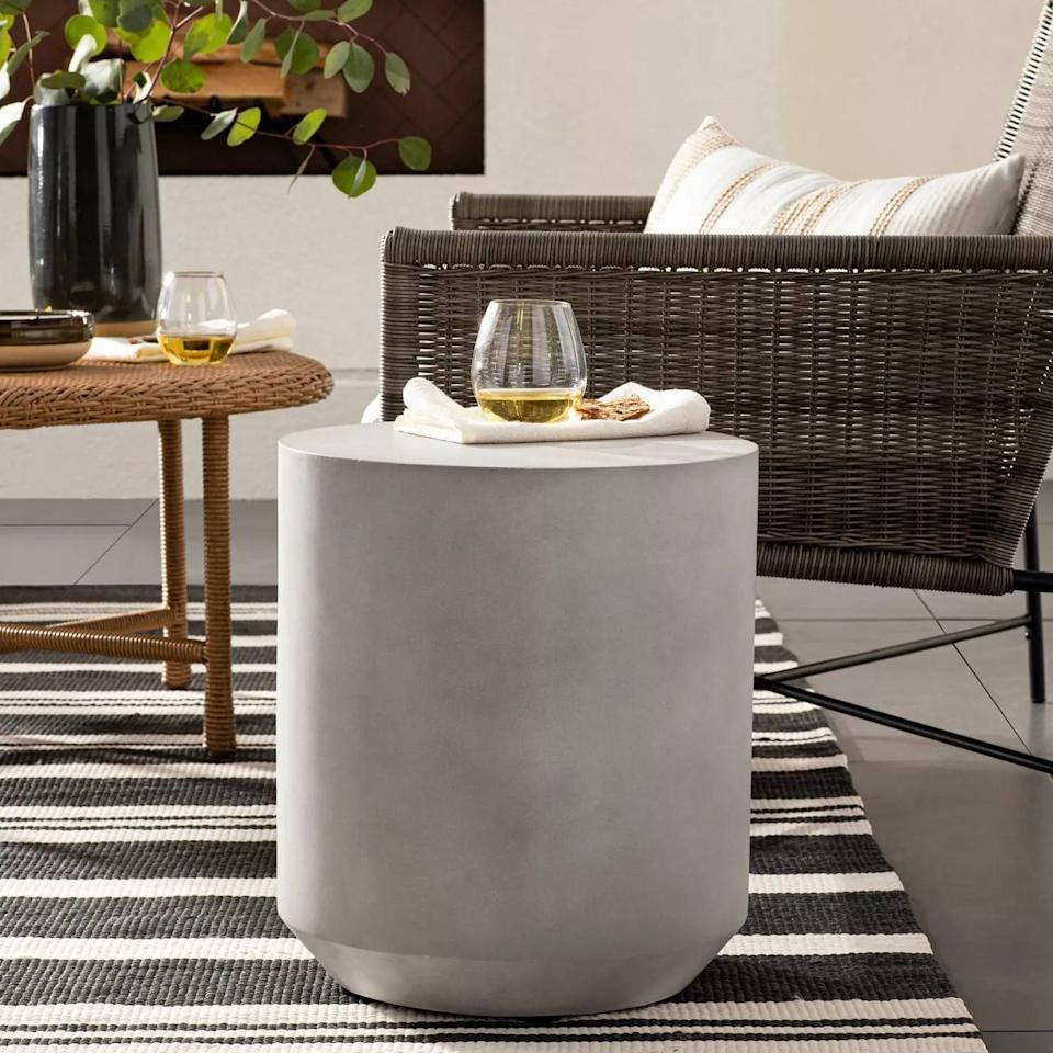 <p>Rest coffee, cocktails, snacks, and whatever else on this <span>Faux Stone Patio Accent Table</span> ($89).</p>
