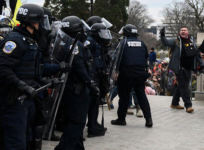 Russ Taylor, right, flips off cops at the Capitol. (Photo: ANDREW CABALLERO-REYNOLDS via Getty Images)