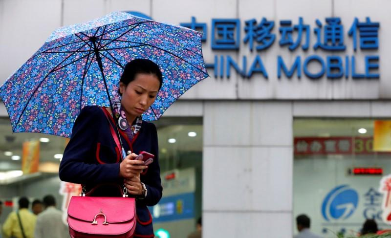 FILE PHOTO: A woman uses her mobile phone in front of a China Mobile office in downtown Shanghai