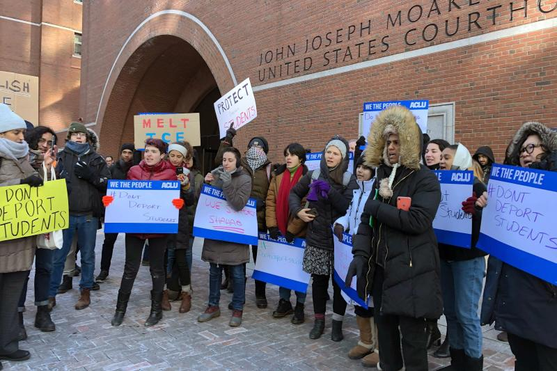 Protesters stand outside the federal courthouse where a hearing was scheduled for Northeastern University student Shahab Dehghani, Tuesday, Jan. 21, 2020, in Boston. Dehghani arrived on a flight into Boston on Monday but was detained by U.S. Customs and Border Patrol at Logan International Airport and then was deported. (AP Photo/Philip Marcelo)