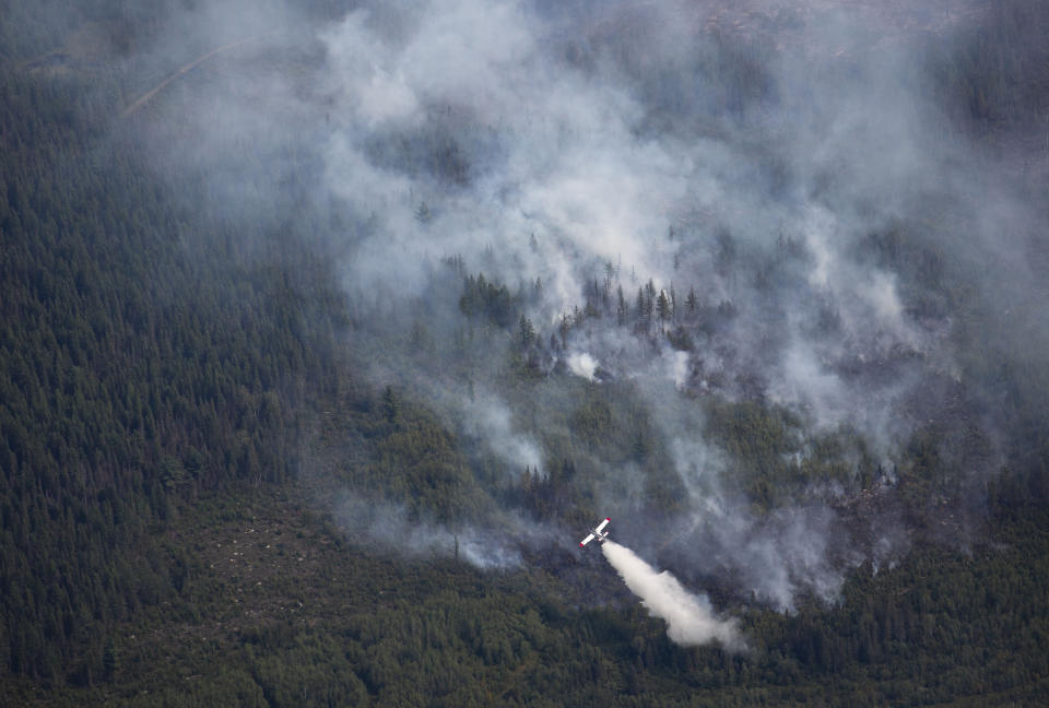 An Aircraft drops water scooped from nearby Sand Lake onto the Greenwood Fire , about 50 miles north of Duluth, Minn., Tuesday, Aug. 17, 2021, as seen from an airplane above the temporary flight restriction zone. (Alex Korman/Star Tribune via AP)