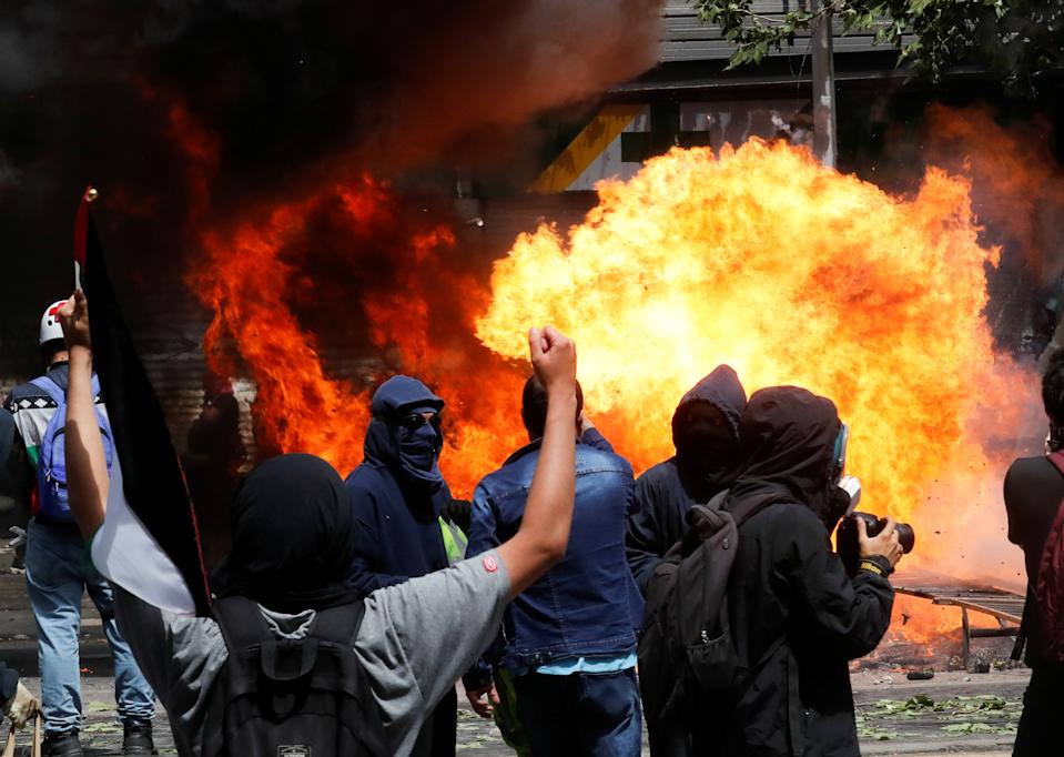 Demonstrators are seen in front of a burning barricade during a protest against Chile's state economic model in Santiago, Chile on Oct. 23, 2019. (Photo: Henry Romero/Reuters)