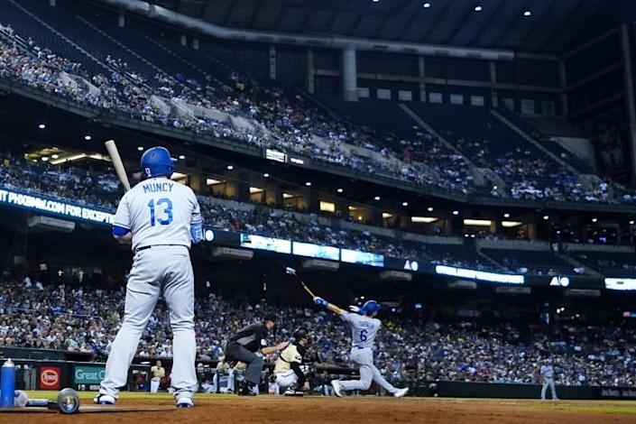 Dodgers' Trea Turner hits a home run as Dodgers' Max Muncy, umpire Chad Whitson and Arizona catcher Carson Kelly look on