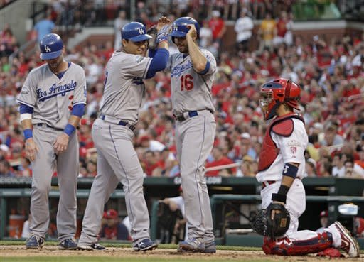 Los Angeles Dodgers' Luis Cruz, center, celebrates with teammates Andre Ethier (16) and Adam Kennedy (3), as St. Louis Cardinals catcher Yadier Molina looks on, after they all scored on Cruz's three-run home run in the second inning of a baseball game, Monday, July 23, 2012 in St. Louis.(AP Photo/Tom Gannam)