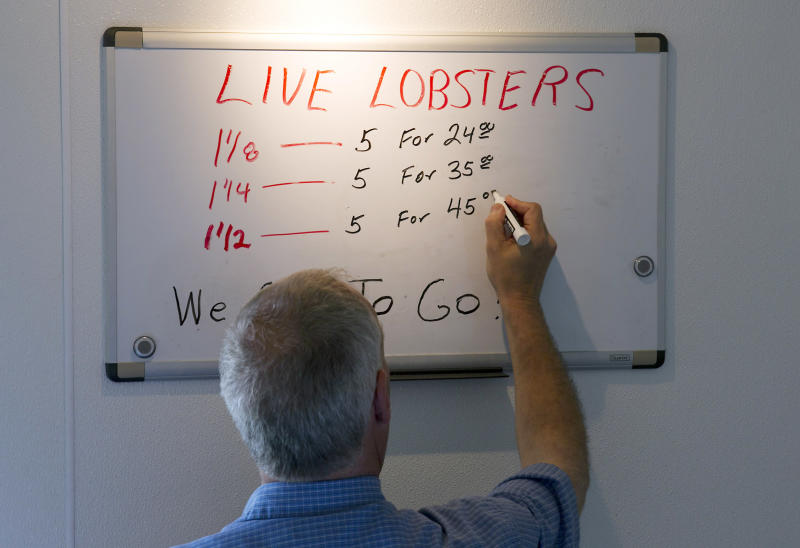 In this photo made Thursday, June 28, 2012, Bob Coppersmith updates the price board at Dock's Seafood Restaurant in South Portland, Maine, dropping the price of five small lobsters down to $24. Many stores are selling the king of seafood for under $5 a pound, making it cheaper than bologna by weight. (AP Photo/Robert F. Bukaty)