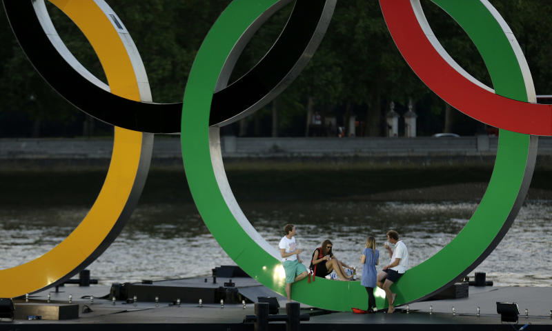 A group sit on a set of Olympic Rings floating in the River Thames off of Battersea park Tuesday, July 24, 2012, in London. The city will host the 2012 London Olympics with opening ceremonies scheduled for Friday, July 27. (AP Photo/Charlie Riedel)