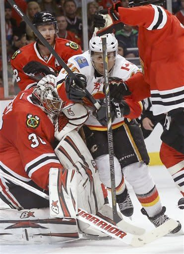 Calgary Flames right wing Jarome Iginla, center, is sandwiched between Chicago Blackhawks goalie Ray Emery (30) and Brent Seabrook during the first period of an NHL hockey game Tuesday, March 26, 2013 in Chicago. (AP Photo/Charles Rex Arbogast)