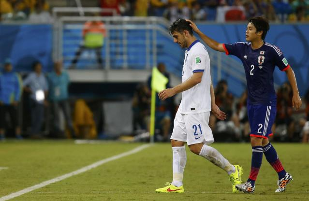Greece's Kostas Katsouranis (L) is consoled by Japan's Atsuto Uchida after Katsouranis is sent off the field with a red card during their 2014 World Cup Group C soccer match at the Dunas arena in Natal June 19, 2014. REUTERS/Kai Pfaffenbach (BRAZIL - Tags: SOCCER SPORT WORLD CUP TPX IMAGES OF THE DAY)