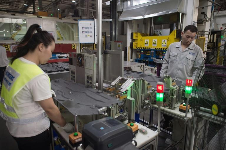 Workers manipulate a machine to make car interior pieces for a major European car maker in the American Industrial Park in Shenyang