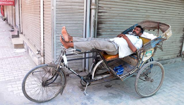A rickshaw puller naps in Patiala, India. (Photo by Bharat Bhushan/Hindustan Times vis Getty Images)