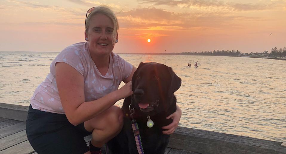 Casey Hyde is pictured with her guide dog Bridget.