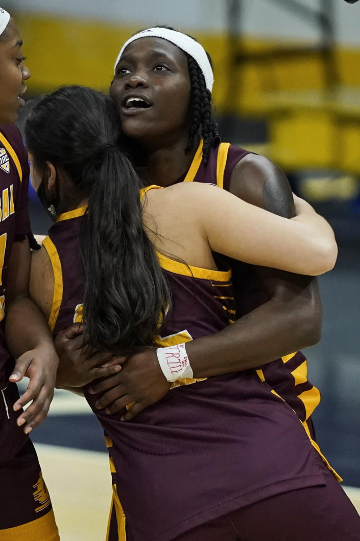 Central Michigan's Micaela Kelly is hugged by a teammate after they defeated Bowling Green 77-72 in an NCAA college basketball game in the championship of the Mid-American Conference tournament, Saturday, March 13, 2021, in Cleveland. (AP Photo/Tony Dejak)