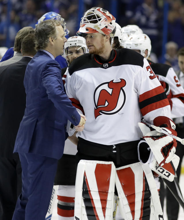 New Jersey Devils goaltender Cory Schneider, right, congratulates Tampa Bay Lightning head coach Jon Cooper after they eliminated the Devils during Game 5 of an NHL first-round hockey playoff series Saturday, April 21, 2018, in Tampa, Fla. (AP Photo/Chris O'Meara)