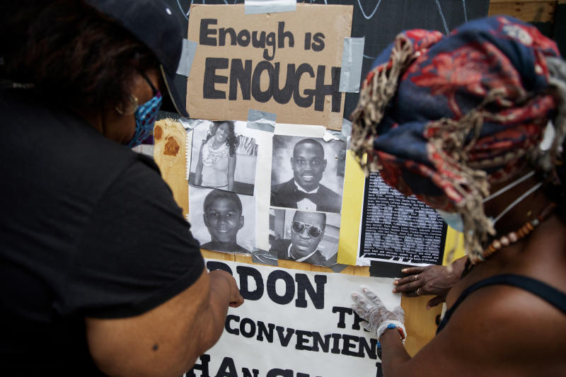 Wendy Long, left, and Sister Mamie, repost signs that were removed form the Lafayette Park parameter fence at the site of protests, Wednesday, June 10, 2020, near the White House in Washington. The protests began over the death of George Floyd, a black man who was in police custody in Minneapolis. Floyd died after being restrained by Minneapolis police officers. (AP Photo/Carolyn Kaster)
