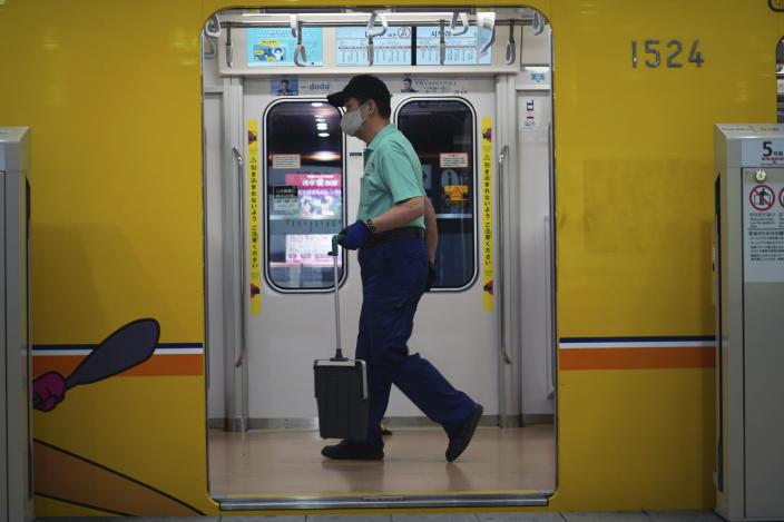 An employee wearing a protective mask to help curb the spread of the coronavirus cleans a subway car Tuesday, Nov. 24, 2020, in Tokyo. The Japanese capital confirmed more than 180 new coronavirus cases on Tuesday. (AP Photo/Eugene Hoshiko)