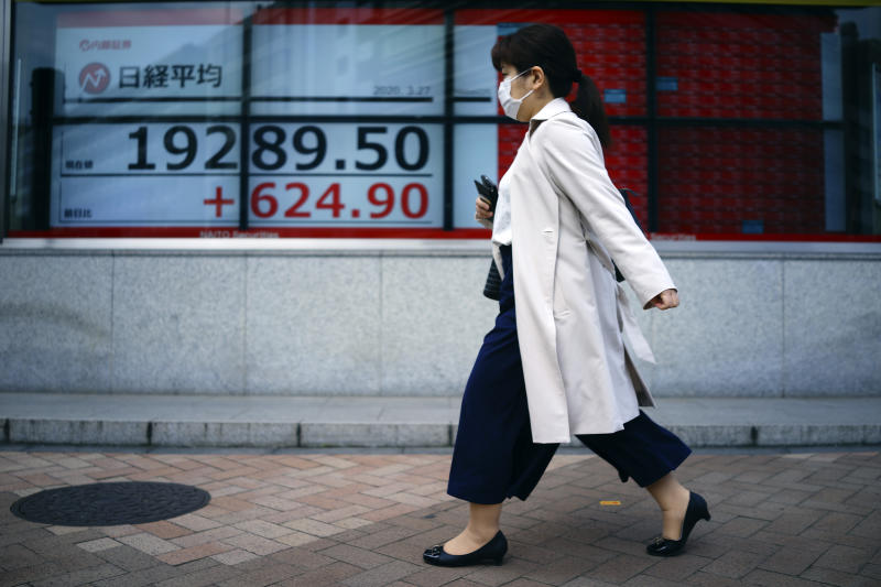 A woman walks past an electronic stock board showing Japan's Nikkei 225 index at a securities firm in Tokyo Friday, March 27, 2020. Shares are mostly higher in Asia after stocks surged again on Wall Street with the approaching approval of a massive coronavirus relief bill by Congress. (AP Photo/Eugene Hoshiko)