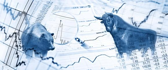 A bear and a bull on top of a collection of charts and data tables.