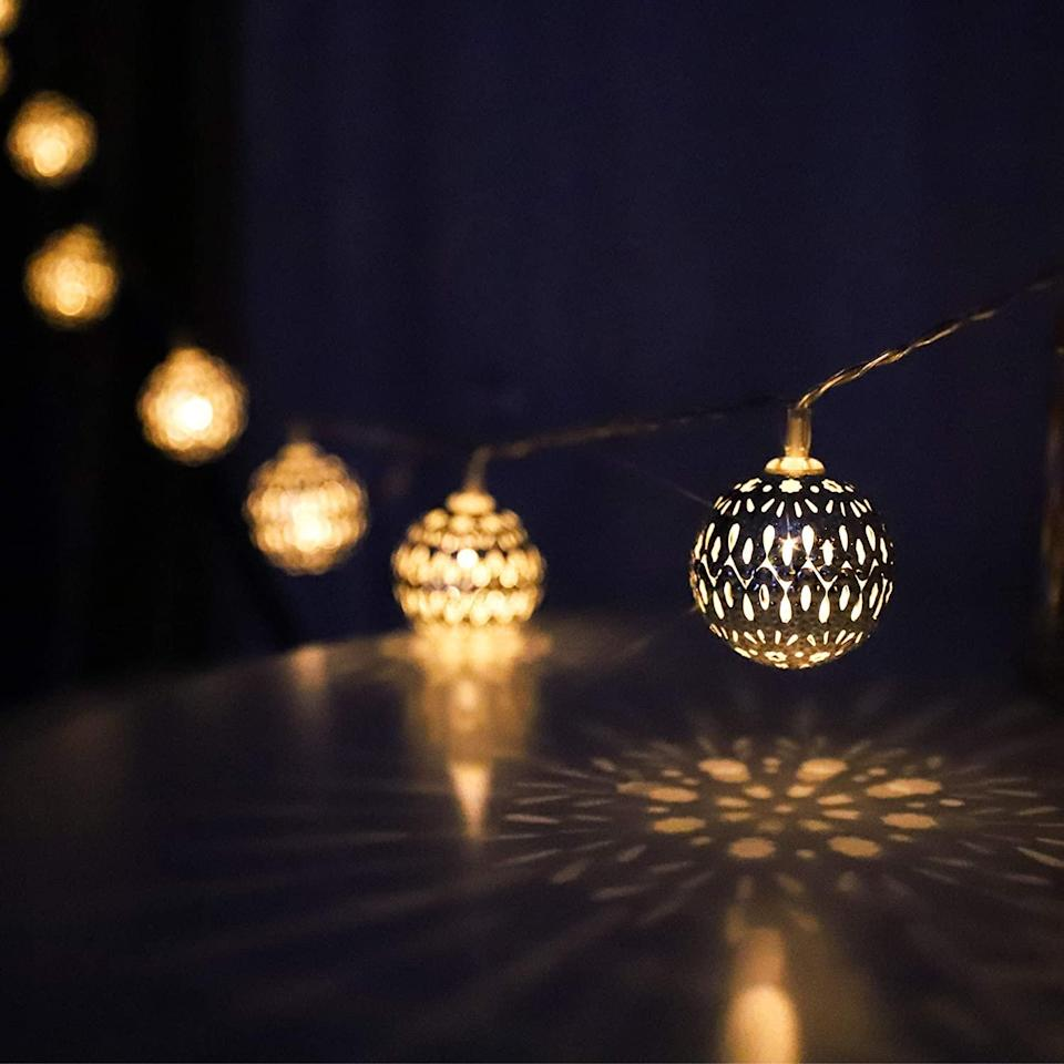 """<p>These battery-powered string lights resemble metal <a href=""""https://www.marthastewart.com/275166/christmas-tree-decorating-ideas"""" rel=""""nofollow noopener"""" target=""""_blank"""" data-ylk=""""slk:Christmas tree ornaments"""" class=""""link rapid-noclick-resp"""">Christmas tree ornaments</a> and cast a warm glow in any area of your home.</p> <p> <strong><em>Shop Now: </em></strong><em>myCozyLite LED Globe String Lights, $13.99, <a href=""""https://www.amazon.com/myCozyLite-Moroccan-Battery-Powered-Pattern/dp/B08HJ2XHFZ/ref=as_li_ss_tl?ie=UTF8&linkCode=ll1&tag=mslholourfavoritechristmaslightscbiggsnov20-20&linkId=7063bfeef4f677149cfcbcd0ff6c922f&language=en_US"""" rel=""""nofollow noopener"""" target=""""_blank"""" data-ylk=""""slk:amazon.com"""" class=""""link rapid-noclick-resp"""">amazon.com</a></em><em>.</em></p>"""
