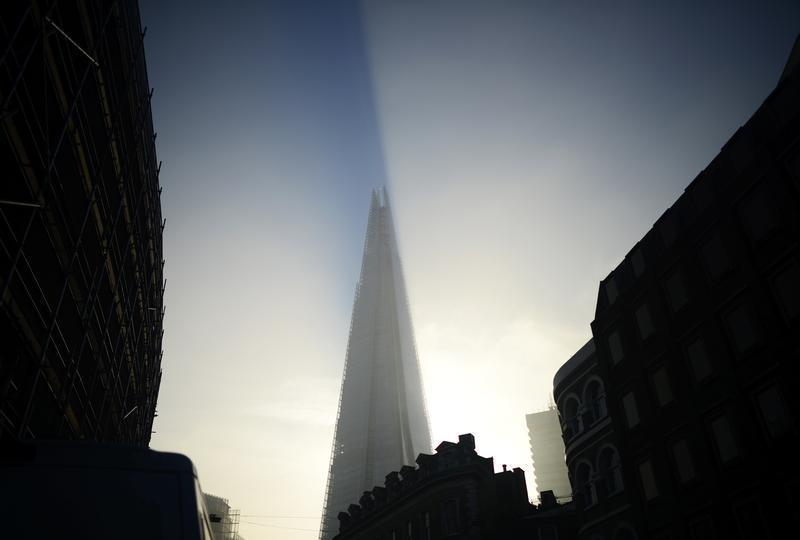 The early morning sun hits The Shard building as fog clears over London