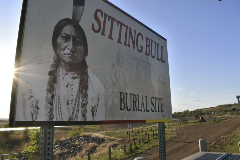 A billboard with a photo of Sitting Bull on it reads 'sitting bull burial site'