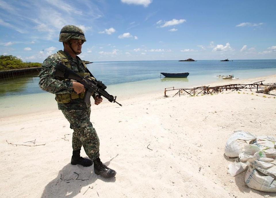 A Philippine soldier patrols a beach on Pagasa Island (Thitu Island) on May 11, 2015 (AFP Photo/Ritchie B. Tongo)