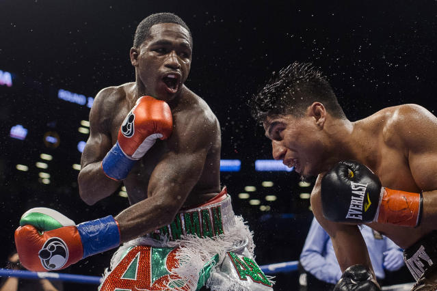Adrien Broner (L) follows through on a punch to Mikey Garcia during a boxing bout at 140 pounds, Saturday, July 29, 2017, in New York. (AP Photo/Andres Kudacki)