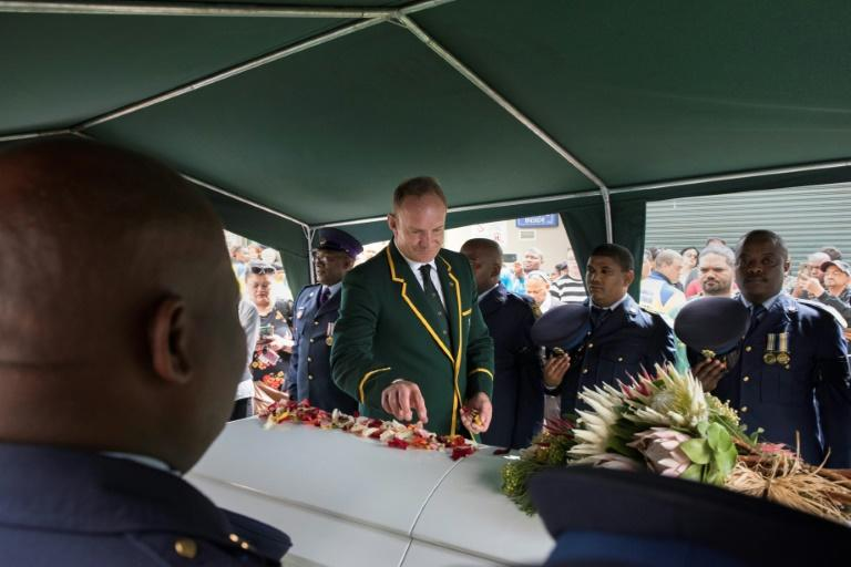 Francois Pienaar, captain of the 1995 South Africa team that won the Rugby World Cup, lays flower petals on the coffin of former teammate Chester Williams in Cape Town Saturday