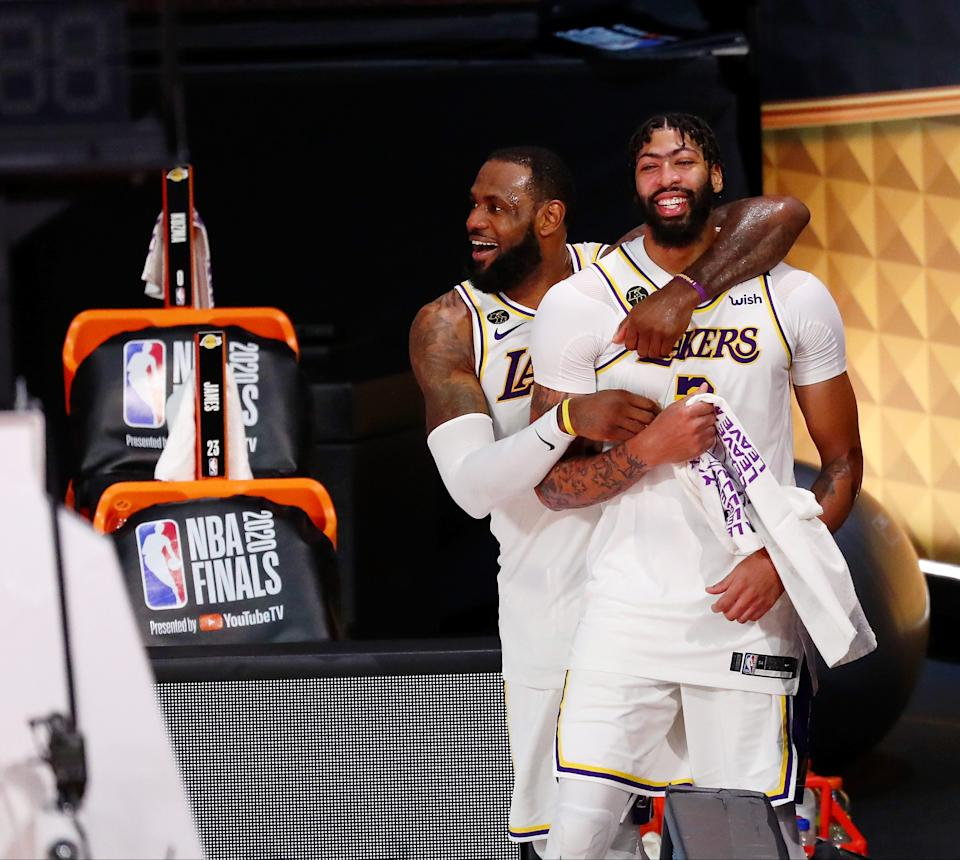 Oct 11, 2020; Lake Buena Vista, Florida, USA; Los Angeles Lakers forward LeBron James (23) and forward Anthony Davis (3) celebrate during the fourth quarter in game six of the 2020 NBA Finals at AdventHealth Arena. The Los Angeles Lakers won 106-93 to win the series.