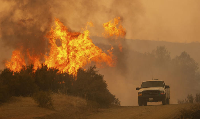 A truck passes by flames during the Ranch Fire in Clearlake Oaks, Calif., on Sunday, Aug. 5, 2018. (AP Photo/Josh Edelson)