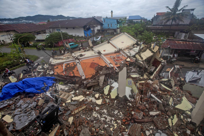 Motorists ride past buildings flattened by an earthquake in Mamuju, West Sulawesi, Indonesia, Saturday, Jan. 16, 2021. Damaged roads and bridges, power blackouts and lack of heavy equipment on Saturday hampered Indonesia's rescuers after a strong and shallow earthquake left a number of people dead and injured on Sulawesi island. (AP Photo/Yusuf Wahil)