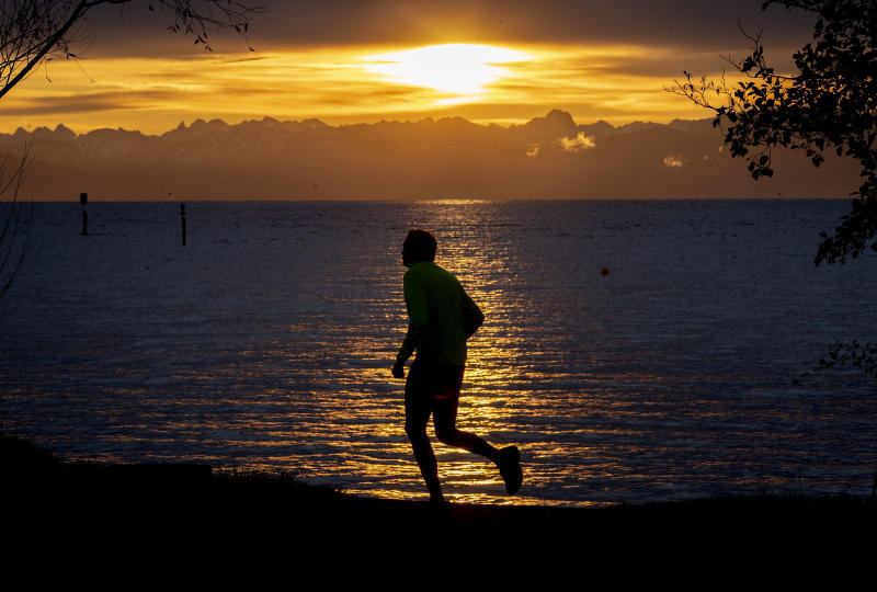 A man runs along the lake of Constance with the Swiss Alps in background during sunrise in Constance, Germany, Thursday, Nov. 14, 2019. (AP Photo/Michael Probst)
