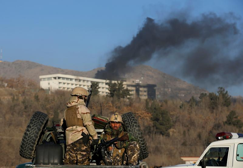 Afghan security forces look on as smoke rises from the Intercontinental Hotel in Kabul on Jan. 21, 2018. (Omar Sobhani / Reuters)