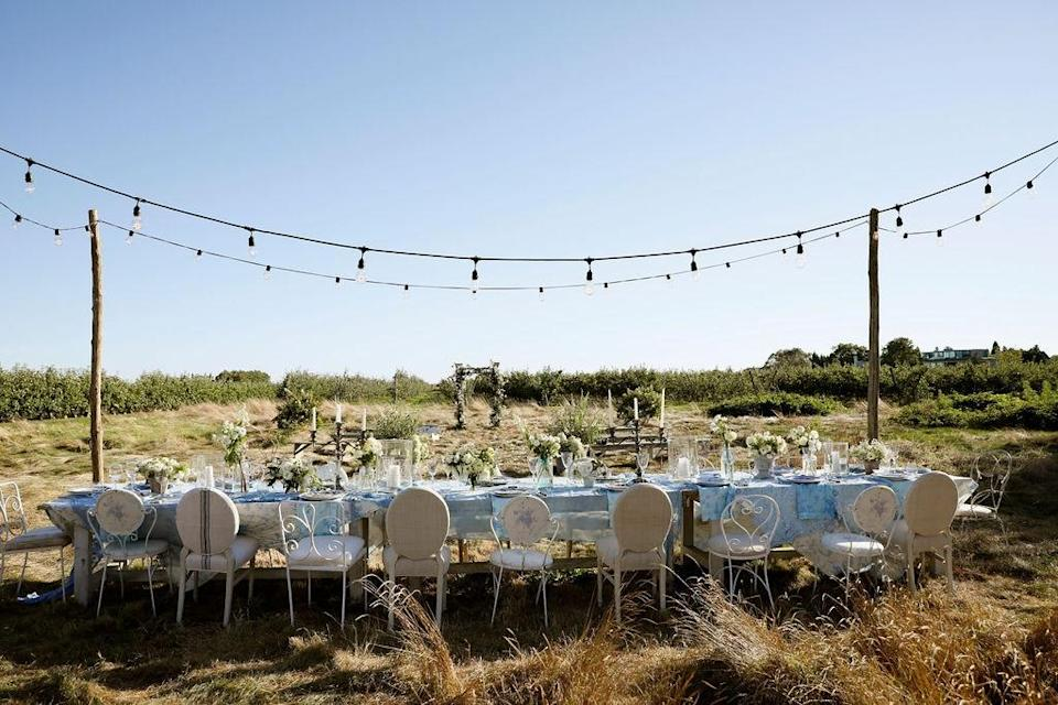 """""""The week before our ceremony we spent hours moving around this farm table to the perfect spot,"""" Dean says. """"We must have tried 5 different options and finally settled on this location. I flanked the table with Cedar poles and strung circus lights between them grounding the entire reception. We also decided to indigo dye vintage pieces of lace to accent and pair with the La Vie en Rose Morning gray tablecloth and napkins from LoveShackFancy Home. Nancy mixed and matched different sets of vintage china and silverware paired to feel more relaxed and spontaneous. We always incorporate the traditions of <em>wabi sabi.</em>"""""""