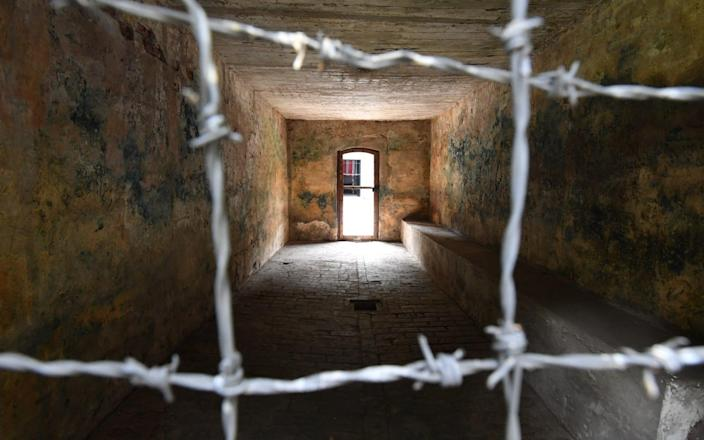 A gas chamber seen through barbed wire - Bruce Adams