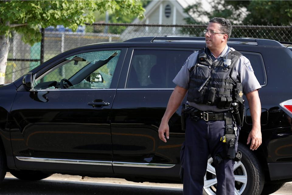 A police officer stands near a damaged vehicle.
