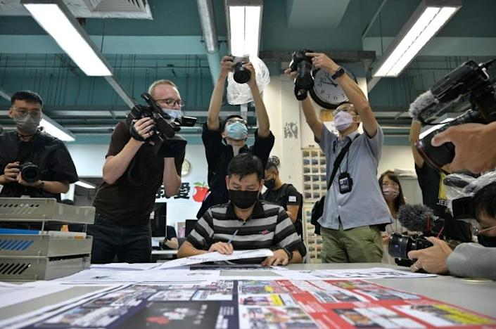 Members of the press take photos as executive editor in chief Lam Man-Chung (C) proof reads the next day's 'Apple Daily' newspaper before it goes to print for the last time