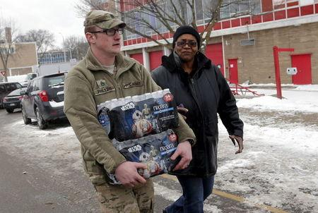 Michigan National Guard Staff Sergeant William Phillips (L) assists a Flint resident with bottled water at a fire station in Flint, Michigan January 13, 2016. REUTERS/Rebecca Cook