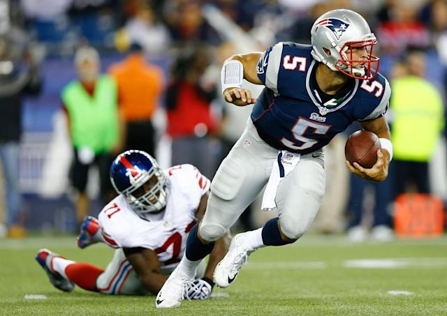 FOXBORO, MA - AUGUST 29: Tim Tebow #5 of the New England Patriots evades a tackle and runs with the ball past Adewale Ojomo #71 of the New York Giants during the preseason game at Gillette Stadium on August 29, 2013 in Foxboro, Massachusetts. (Photo by Jared Wickerham/Getty Images)