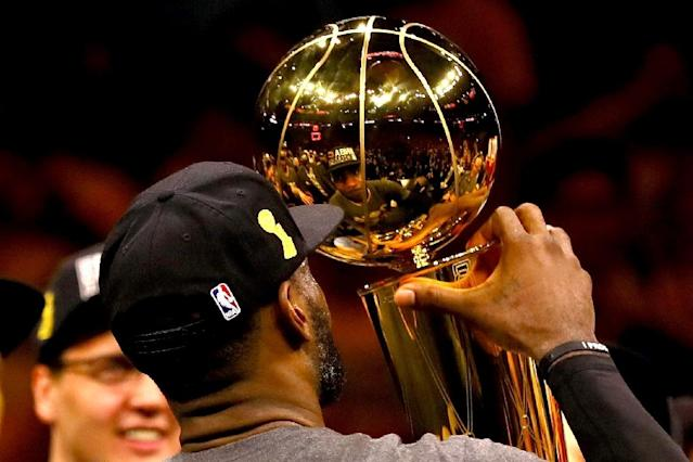 LeBron James of the Cleveland Cavaliers holds the Larry O'Brien Championship Trophy after victory against the Golden State Warriors in Game 7 of the NBA Finals in Oakland, California, on June 19, 2016 (AFP Photo/Ezra Shaw)