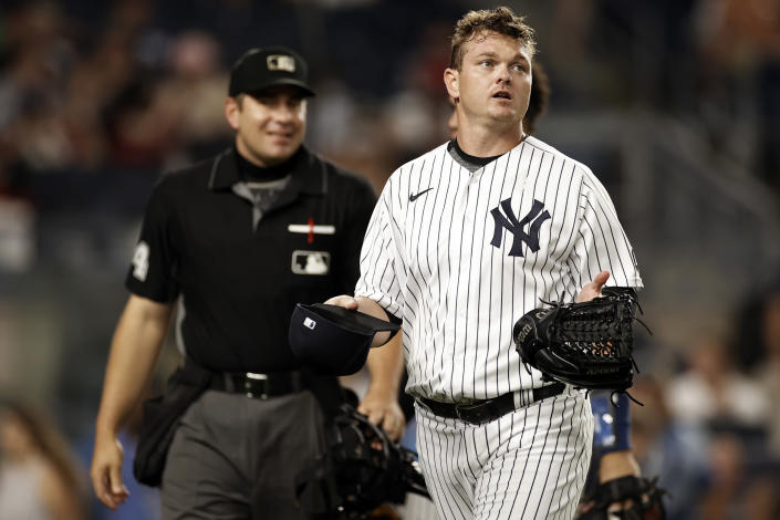 New York Yankees relief pitcher Justin Wilson holds out his hat and glove after they were checked by umpires during the fourth inning of the team's baseball game against the Los Angeles Angels on Wednesday, June 30, 2021, in New York. (AP Photo/Adam Hunger)