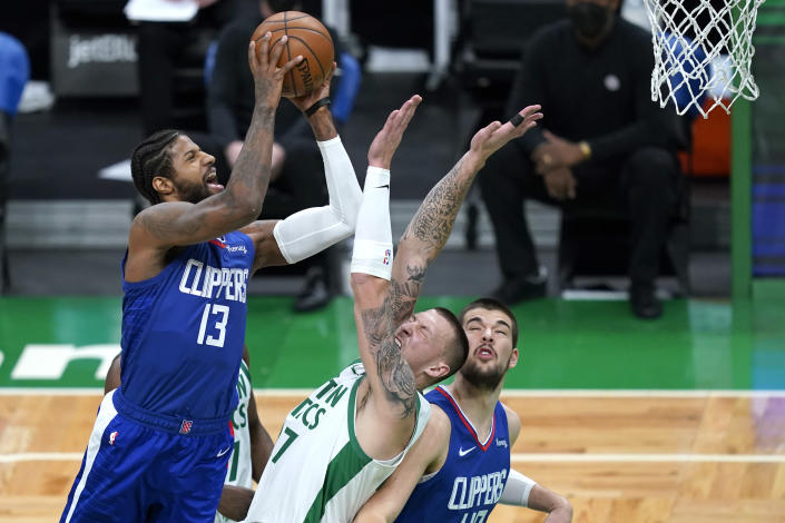Los Angeles Clippers guard Paul George (13) shoots against Boston Celtics center Daniel Theis (27) as Clippers center Ivica Zubac (40) looks on in the first quarter of an NBA basketball game, Tuesday, March 2, 2021, in Boston. (AP Photo/Elise Amendola)