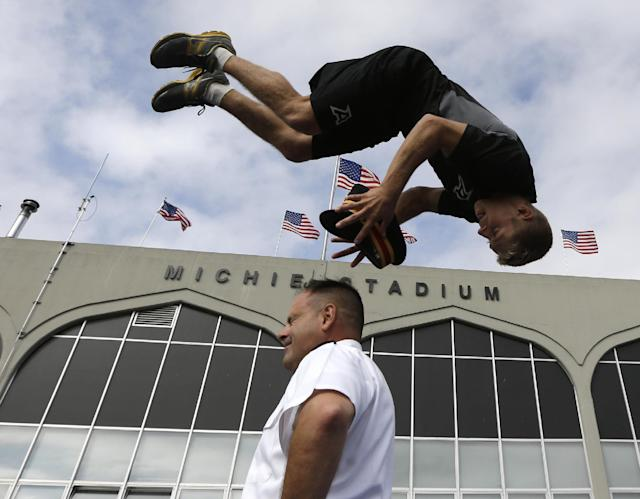 Army gymnastics team member Kip Webber of Boxborough, Mass., grabs the hat from Col. Joseph DeAntona, deputy military athletic director, during a demonstration outside Michie Stadium before an NCAA college football game between Army and Wake Forest on Saturday, Sept. 21, 2013, in West Point, N.Y. (AP Photo/Mike Groll)