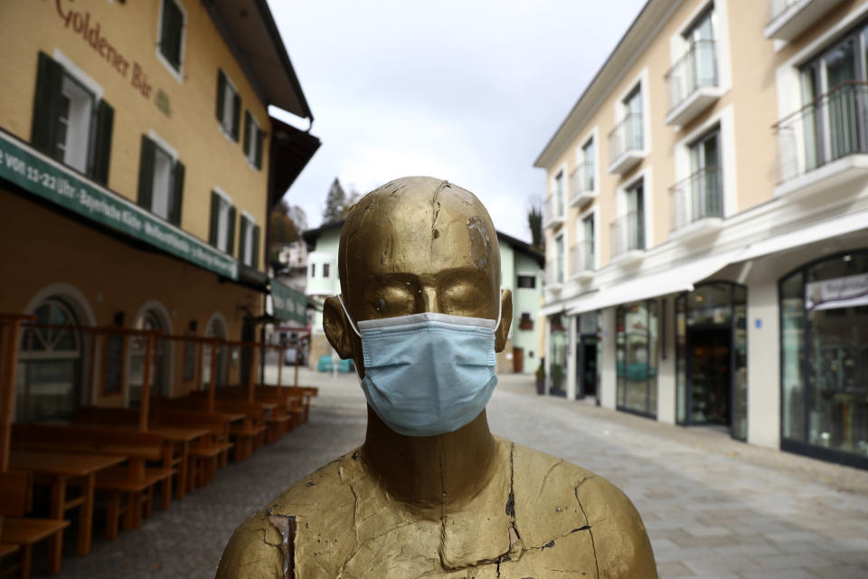 A art sculpture wearing a face mask in the deserted city of Berchtesgaden, Germany, Monday, Oct. 26, 2020. Authorities have posed the Berchtesgaden region under a lockdown since Oct. 20, 2020 due to a rising number of cases of the pandemic COVID-19 disease caused by the SARS-CoV-2 coronavirus in the district of Berchtesgadener Land. Local authorities in Bavaria's Rottal-Inn county, on the border with Austria, said Monday that the restrictions will begin at midnight. (AP Photo/Matthias Schrader)