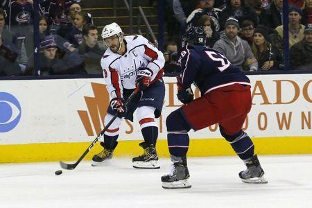 Dec 8, 2018; Columbus, OH, USA; Washington Capitals left wing Alex Ovechkin (8) chips the puck past Columbus Blue Jackets defenseman David Savard (58) during the first period at Nationwide Arena. Russell LaBounty-USA TODAY Sports