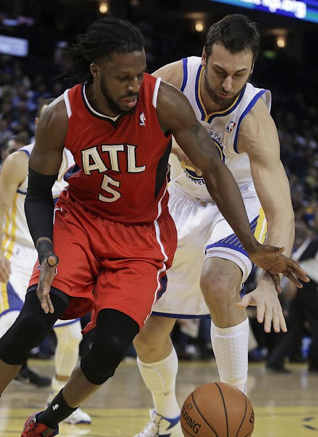 Atlanta Hawks' DeMarre Carroll (5) and Golden State Warriors' Andrew Bogut chase a loose ball during the first half of an NBA basketball game Friday, March 7, 2014, in Oakland, Calif. (AP Photo/Ben Margot)