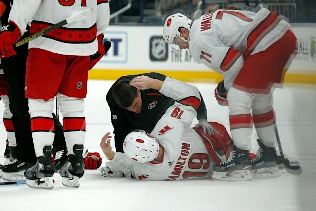COLUMBUS, OH - JANUARY 16: Dougie Hamilton #19 of the Carolina Hurricanes is checked on by head athletic trainer Doug Bennett after getting injured during the second period against the Columbus Blue Jackets on January 16, 2020 at Nationwide Arena in Columbus, Ohio. (Photo by Kirk Irwin/Getty Images)