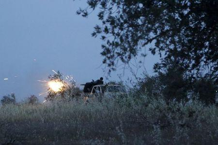 Rebel fighters of the Al-Furqan brigade fire their weapon during what they said is an offensive to take control of the al-Mastouma army base which is controlled by forces loyal to Syria's President Bashar al-Assad near Idlib city May 17, 2015. Picture taken May 17, 2015. REUTERS/Khalil Ashawi