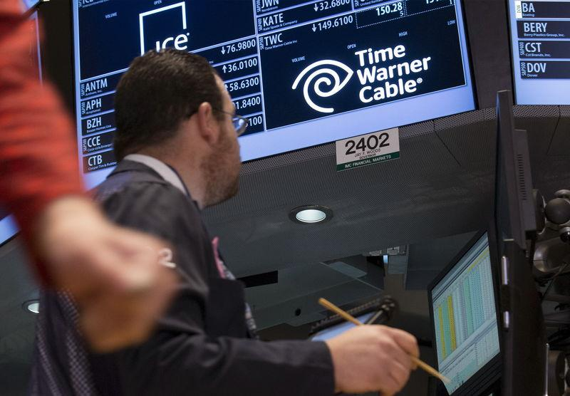 Traders work by the post that trades Time Warner Cable stock on the floor of the New York Stock Exchange
