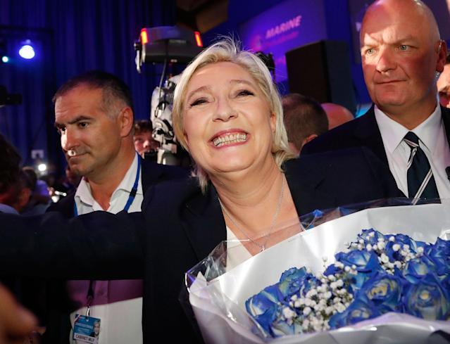 <p>Far-right leader and candidate for the 2017 French presidential election, Marine Le Pen, surrounded by bodyguards, celebrates with supporters while holding a bunch of flowers after exit poll results of the first round of the presidential election were announced at her election day headquarters in Henin-Beaumont, northern France, Sunday, April 23, 2017. Polling agency projections show far-right leader Marine Le Pen and centrist Emmanuel Macron leading in the first-round French presidential election. (AP Photo/Frank Augstein) </p>