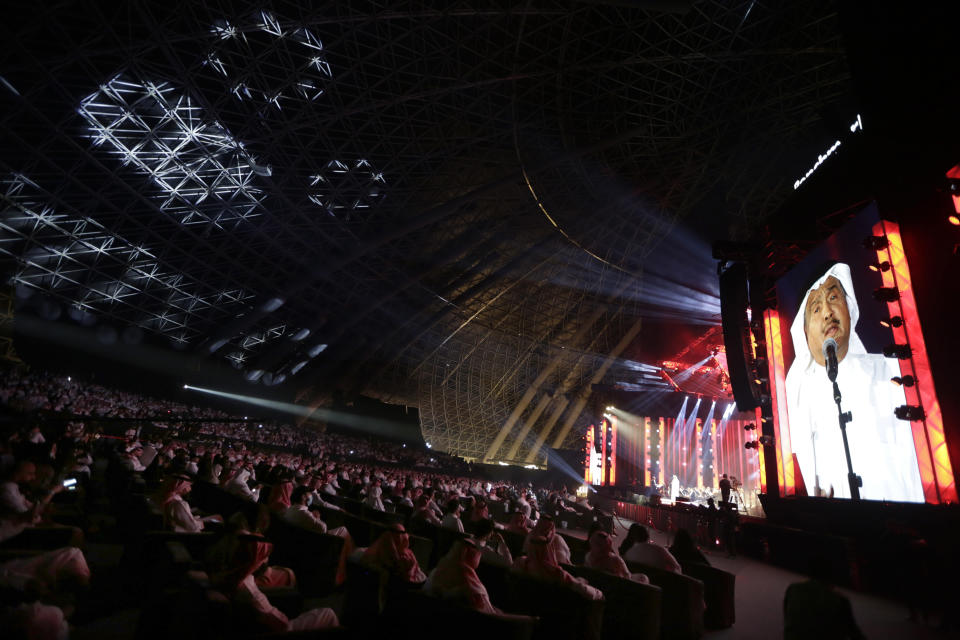 In this July 8, 2021 photo, audience members cheer as Saudi prominent singer Mohammed Abdu, viewed on the screen, performs onstage at the newly built Super Dome, in Jiddah, Saudi Arabia. The cloud of social restrictions that loomed over generations of Saudis is quickly dissipating and the country is undergoing visible change. Still, for countless numbers of people in the United States and beyond, Saudi Arabia will forever be associated with 9/11. (AP Photo/Amr Nabil)